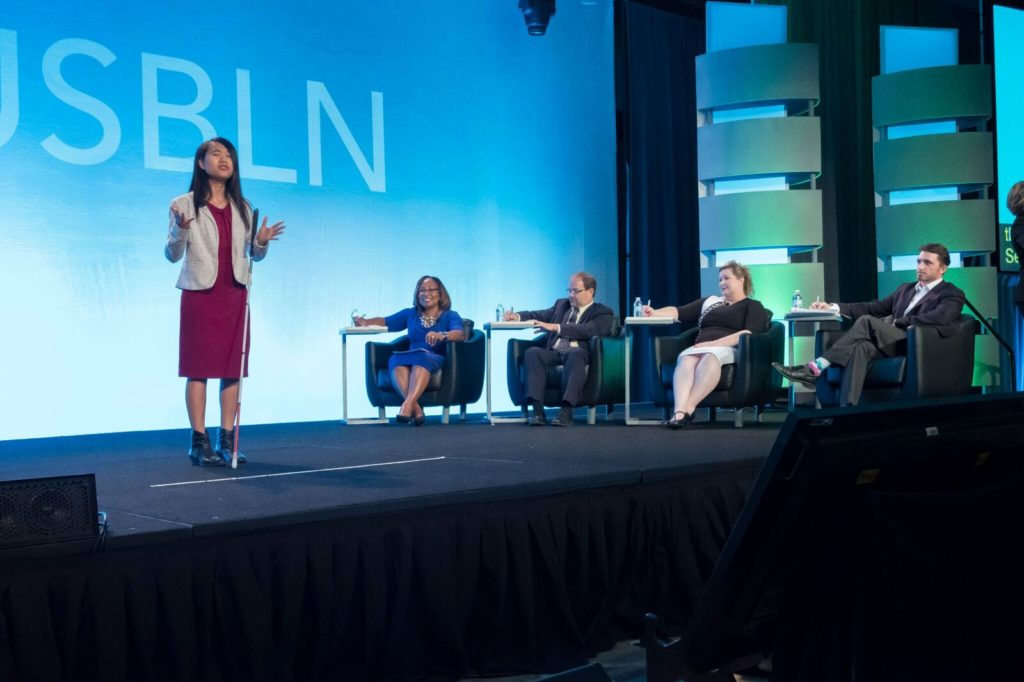 Rising Leader presents a business pitch in front of a panel of experts.
